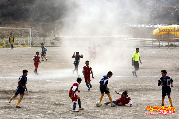 THIMPHU, BHUTAN - MARCH 31: Soccer players from the Loselling Lower Secondary school play against the Jigme Losel Primary school in the finals of a local soccer match as the strong winds blow March 31, 2008 in Thimphu, Bhutan. The Bhutanese often wear the traditional national dress which is a kimono-like gown called a gho, and all students must wear it as a school uniform. The Bhutanese culture ministry feels that the dress code is about national identity and worries about the forces of globalization threatening the nation's youth. Bhutan's youth today have embraced Western styles and with cable TV, internet cafes and video gaming making it easier for them to be a part of the global culture. A new era of democracy is being ushered into the tiny Himalayan nation after the country held a successful  national elections ending a century of rule by absolute monarchy.  (Photo by Paula Bronstein/Getty Images)