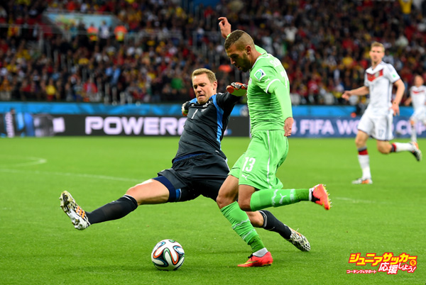PORTO ALEGRE, BRAZIL - JUNE 30: Islam Slimani of Algeria tries to shoot at goal while Manuel Neuer of Germany tackles to block outside the penalty area during the 2014 FIFA World Cup Brazil Round of 16 match between Germany and Algeria at Estadio Beira-Rio on June 30, 2014 in Porto Alegre, Brazil.  (Photo by Mike Hewitt - FIFA/FIFA via Getty Images)