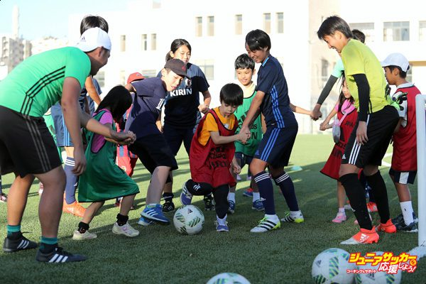 AMMAN, JORDAN - SEPTEMBER 27:  Young local Japanese children play football with the Japan team during the Japan Training and Japanese local community visit at the Polo 1 Sports City on September 27, 2016 in Amman, Jordan.  (Photo by Christopher Lee - FIFA/FIFA via Getty Images)