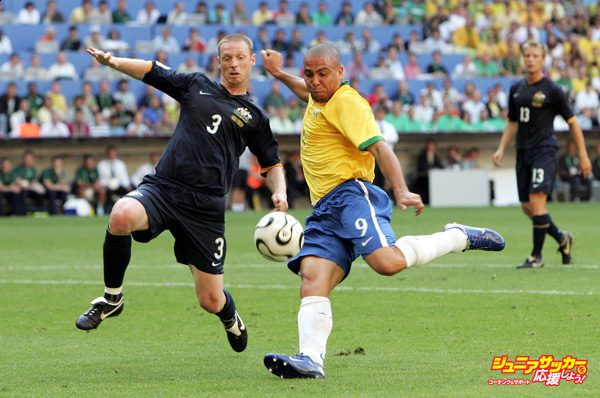 MUNICH, GERMANY - JUNE 18:  Ronaldo of Brazil has a shot on goal as Craig Moore of Australia tries to block during the FIFA World Cup Germany 2006 Group F match between Brazil and  Australia at the Stadium Munich on June 18, 2006 in Munich, Germany.  (Photo by Phil Cole/Getty Images)