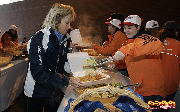 BOSTON - APRIL 15: Angela Estey, left, of Edmonton, Alberta, Canada, a Boston Marathon runner, is served by Martha Keller of Wellesley College, right, as runners, their families and volunteers take part in the pre-race dinner held at City Hall Plaza in Boston, Mass. on Sunday, April 15, 2007. (Photo by John Bohn/The Boston Globe via Getty Images)