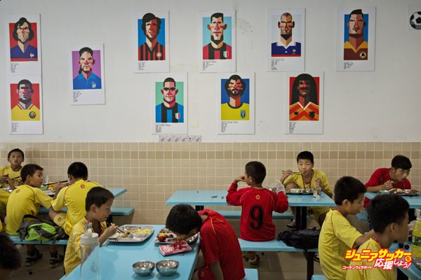 QINGYUAN, CHINA - JUNE 12:  Young Chinese football players eat lunch under caricatures of famous footballers in the canteen at the Evergrande International Football School on June 12, 2014 near Qingyuan in Guangdong Province, China. The sprawling 167-acre campus is the brainchild of property tycoon Xu Jiayin, whose ambition is to train a generation of young athletes to establish China as a football powerhouse. The school is considered the largest football academy in the world with 2400 students, more than 50 pitches and a squad of Spanish coaches through a partnership with Real Madrid. (Photo by Kevin Frayer/Getty Images)
