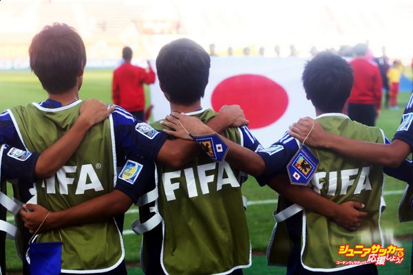 SHARJAH, UNITED ARAB EMIRATES - OCTOBER 28:  Substitution players of Japan sing their national anthem prior to the FIFA U-17 World Cup UAE 2013 Round of 16 match between Japan and Sweden at Sharjah Stadium on October 28, 2013 in Sharjah, United Arab Emirates.  (Photo by Alex Grimm - FIFA/FIFA via Getty Images)