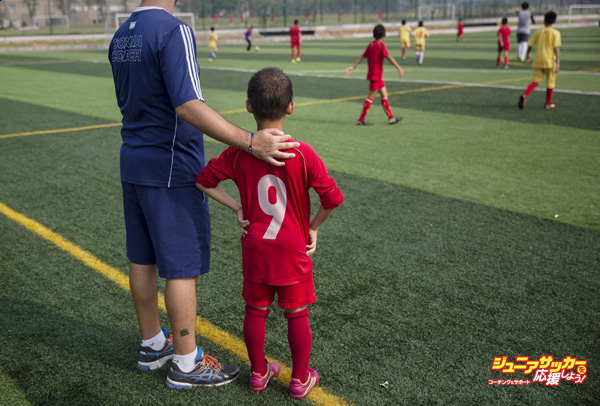 QINGYUAN, CHINA - JUNE 14:  A coach from Real Madrid stands with a young Chinese student before subbing him to a training match at the Evergrande International Football School on June 14, 2014 near Qingyuan in Guangdong Province, China. The sprawling 167-acre campus is the brainchild of property tycoon Xu Jiayin, whose ambition is to train a generation of young athletes to establish China as a football powerhouse. The school is considered the largest football academy in the world with 2400 students, more than 50 pitches and a squad of Spanish coaches through a partnership with Real Madrid. (Photo by Kevin Frayer/Getty Images)