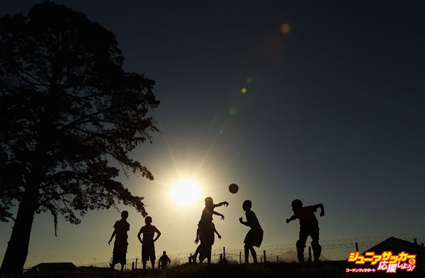 GEORGE, SOUTH AFRICA - JUNE 25:  Children play football as they wait for the arrival of the Japan football team at the Lawaaikamp Sport ground for township visit during the FIFA 2010 World Cup on June 25, 2010 in George, South Africa.  (Photo by Mark Kolbe/Getty Images)