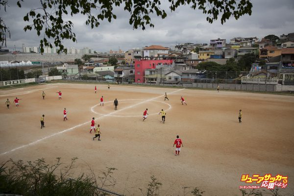SAO PAULO, BRAZIL - JUNE 21:  Men play football on the 'Artur Alvim' club's dirt pitch in the poor neighbourhood of Itaquera, adjacent to the 'Arena de Sao Paulo' stadium, on June 21, 2014 in Sao Paulo, Brazil. The Arena de Sao Paulo, which is reported to have cost in excess of 200 million GBP, hosted the opening match of the 2014 FIFA World Cup and has a capacity of over 61,000. The total cost borne by Brazil for staging the 2014 World Cup is estimated to be 6.5 billion GBP, which critics have argued would have better spent on the millions of Brazilians living in poverty.  (Photo by Oli Scarff/Getty Images)
