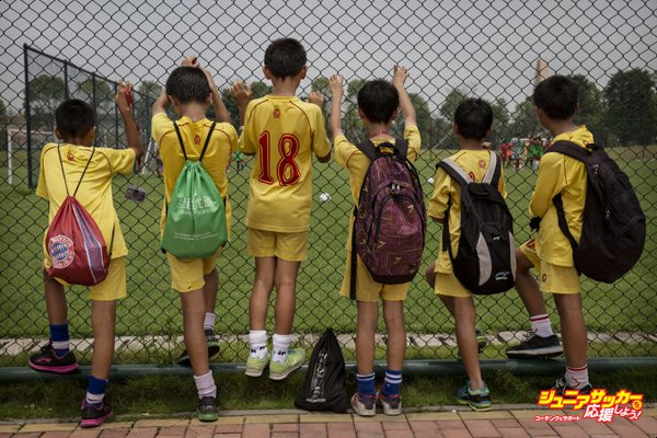 QINGYUAN, CHINA - JUNE 12:  Young Chinese football players watch others training at the Evergrande International Football School on June 12, 2014 near Qingyuan in Guangdong Province, China. The sprawling 167-acre campus is the brainchild of property tycoon Xu Jiayin, whose ambition is to train a generation of young athletes to establish China as a football powerhouse. The school is considered the largest football academy in the world with 2400 students, more than 50 pitches and a squad of Spanish coaches through a partnership with Real Madrid. (Photo by Kevin Frayer/Getty Images)